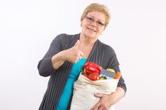 Ανώτερη γυναίκα με την τσάντα αγορών και την πιστωτική κάρτα που παρουσιάζουν αντίχειρες, που πληρώνουν για τις αγορές στοκ εικόνα