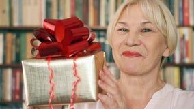 Ανώτερη γυναίκα με το παρόν Συνταξιούχος που κρατά το χρυσό κιβώτιο δώρων με τα κόκκινα γενέθλια εορτασμού κορδελλών απόθεμα βίντεο