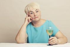 Ανώτερη γυναίκα με το ποτήρι του άσπρου κρασιού Στοκ Εικόνες