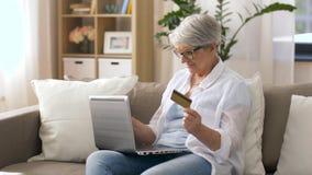 Ανώτερη γυναίκα με το lap-top και την πιστωτική κάρτα στο σπίτι φιλμ μικρού μήκους