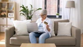 Ανώτερη γυναίκα με το lap-top και την πιστωτική κάρτα στο σπίτι απόθεμα βίντεο