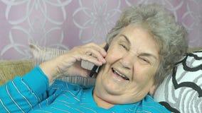 Ανώτερη γυναίκα με το smartphone που καλεί στο δωμάτιο φιλμ μικρού μήκους