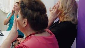 Ανώτερη γυναίκα ομάδας που κάνει το αντι μασάζ προσώπου γήρανσης στην κύρια κατηγορία στο σχολείο ομορφιάς Ανώτερα καλλυντικά εκμ απόθεμα βίντεο