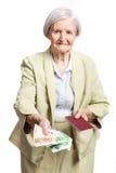 Ανώτερη γυναίκα που δίνει τα χρήματα και που κρατά το διαβατήριο Στοκ Εικόνες
