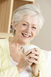 Ανώτερη γυναίκα που απολαμβάνει το ζεστό ποτό Στοκ Εικόνες