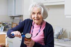 Ανώτερη γυναίκα που βγάζει το καπάκι από το βάζο με την ενίσχυση κουζινών στοκ φωτογραφία με δικαίωμα ελεύθερης χρήσης