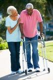 Ανώτερη γυναίκα που βοηθά το σύζυγο με το πλαίσιο περπατήματος στοκ φωτογραφία