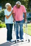 Ανώτερη γυναίκα που βοηθά το σύζυγο με το πλαίσιο περπατήματος στοκ φωτογραφίες