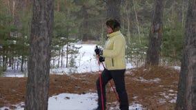 Ανώτερη γυναίκα που εκπαιδεύει το σκανδιναβικό περίπατο κατά τη διάρκεια της πεζοπορίας στο χειμερινό δάσος φιλμ μικρού μήκους