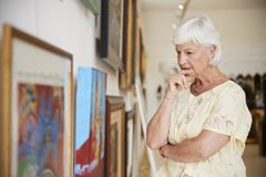 Ανώτερη γυναίκα που εξετάζει τα έργα ζωγραφικής στο γκαλερί τέχνης στοκ φωτογραφία με δικαίωμα ελεύθερης χρήσης