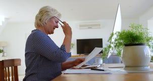 Ανώτερη γυναίκα που εξετάζει το έγγραφο στο σπίτι 4k απόθεμα βίντεο
