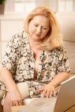 Ανώτερη γυναίκα που εργάζεται με τον υπολογιστή Στοκ Εικόνες