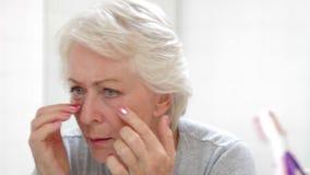 Ανώτερη γυναίκα που ελέγχει το δέρμα στον καθρέφτη λουτρών φιλμ μικρού μήκους
