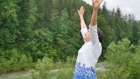 Ανώτερη γυναίκα που κάνει μια τεντώνοντας άσκηση για τα ανώτερα όπλα έξω πέρα από το τοπίο του δάσους και των βουνών φιλμ μικρού μήκους