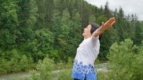 Ανώτερη γυναίκα που κάνει μια τεντώνοντας άσκηση για τα ανώτερα όπλα έξω πέρα από το τοπίο του δάσους και των βουνών απόθεμα βίντεο