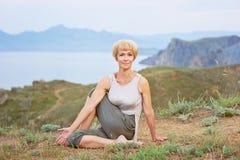 Ανώτερη γυναίκα που κάνει τις ασκήσεις γιόγκας στοκ εικόνα
