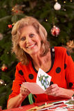 Ανώτερη γυναίκα που κάνει τις κάρτες Χριστουγέννων στο σπίτι Στοκ Φωτογραφίες
