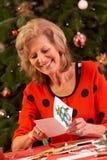 Ανώτερη γυναίκα που κάνει τις κάρτες Χριστουγέννων Στοκ Εικόνα