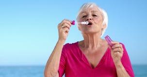 Ανώτερη γυναίκα που κάνει τις φυσαλίδες φιλμ μικρού μήκους