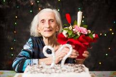 Ανώτερη γυναίκα που κρατά ένα παρόν γενεθλίων στοκ εικόνα με δικαίωμα ελεύθερης χρήσης