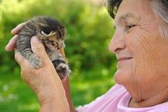 Ανώτερη γυναίκα που κρατά λίγο γατάκι Στοκ Φωτογραφία