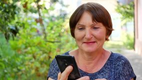 Ανώτερη γυναίκα που κρατά το έξυπνο τηλέφωνο φιλμ μικρού μήκους