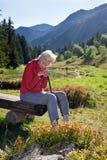 Ανώτερη γυναίκα που κλίνει στο περπάτημα της μπριζόλας στα βουνά στοκ φωτογραφίες