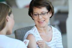 Ανώτερη γυναίκα που παίρνει έναν εμβολιασμό στοκ φωτογραφία