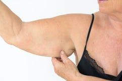 Ανώτερη γυναίκα που παρουσιάζει πλαδαρό βραχίονα, επίδραση της γήρανσης Στοκ φωτογραφία με δικαίωμα ελεύθερης χρήσης