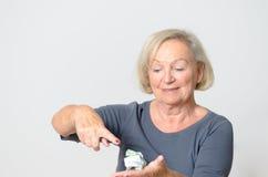 Ανώτερη γυναίκα που παρουσιάζει τσαλακωμένα χρήματα σε διαθεσιμότητα Στοκ Εικόνες