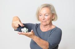 Ανώτερη γυναίκα που παρουσιάζει τσαλακωμένα χρήματα σε διαθεσιμότητα Στοκ Εικόνα