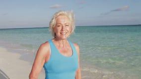 Ανώτερη γυναίκα που περπατά στην όμορφη παραλία φιλμ μικρού μήκους