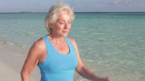 Ανώτερη γυναίκα που περπατά στην όμορφη παραλία απόθεμα βίντεο