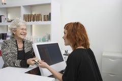 Ανώτερη γυναίκα που πληρώνει για το κούρεμά της στο γραφείο υποδοχής στοκ φωτογραφίες με δικαίωμα ελεύθερης χρήσης