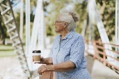 Ανώτερη γυναίκα που στέκεται σε μια γέφυρα με έναν καφέ στοκ φωτογραφίες