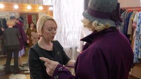 Ανώτερη γυναίκα που τίθεται στο παλτό και το καπέλο στο κατάστημα μόδας φιλμ μικρού μήκους
