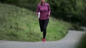 Ανώτερη γυναίκα που τρέχει στην περιοχή λιμνών απόθεμα βίντεο
