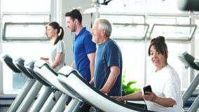 Ανώτερη γυναίκα που τρέχει treadmill στη γυμναστική απόθεμα βίντεο