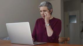 Ανώτερη γυναίκα που υφίσταται τον πονοκέφαλο μετά από την εργασία απόθεμα βίντεο