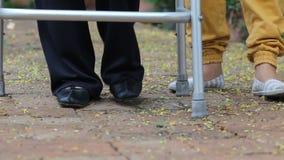Ανώτερη γυναίκα που χρησιμοποιεί έναν περιπατητή με το caregiver στο πάρκο απόθεμα βίντεο