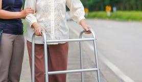 Ανώτερη γυναίκα που χρησιμοποιεί μια διαγώνια οδό περιπατητών με το caregiver στοκ φωτογραφία