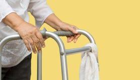 Ανώτερη γυναίκα που χρησιμοποιεί μια διαγώνια οδό περιπατητών με το caregiver στοκ φωτογραφία με δικαίωμα ελεύθερης χρήσης