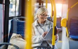Ανώτερη γυναίκα που χρησιμοποιεί την ταμπλέτα, οδηγώντας το δημόσιο λεωφορείο στοκ εικόνες