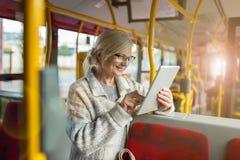 Ανώτερη γυναίκα που χρησιμοποιεί την ταμπλέτα, οδηγώντας το δημόσιο λεωφορείο στοκ φωτογραφίες