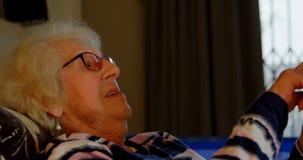 Ανώτερη γυναίκα που χρησιμοποιεί την ψηφιακή ταμπλέτα στην κρεβατοκάμαρα 4k απόθεμα βίντεο