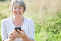 Ανώτερη γυναίκα που χρησιμοποιεί το έξυπνο τηλέφωνο Στοκ Εικόνες