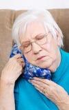Ανώτερη γυναίκα που χρησιμοποιεί το ιατρικό καυτό πακέτο χορταριών Στοκ Εικόνες