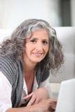 Ανώτερη γυναίκα που χρησιμοποιεί το lap-top στοκ φωτογραφίες
