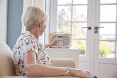 Ανώτερη γυναίκα σε μια πολυθρόνα που ακούει το ραδιόφωνο στο σπίτι στοκ εικόνες