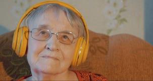 Ανώτερη γυναίκα στα ακουστικά που ακούει τη μουσική απόθεμα βίντεο
